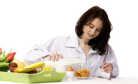 young woman at breakfast pouring milk in corn flakes photo