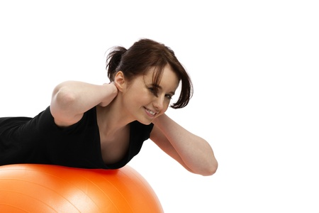 with orange and white body: young woman exercising with orange exercise ball