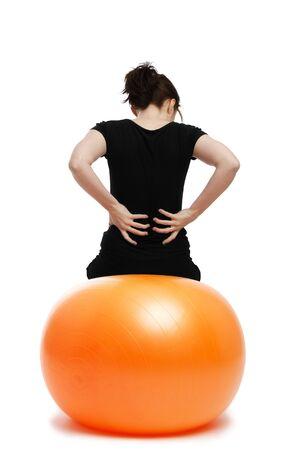 dolor muscular: mujer joven con dolor en la espalda, sentado en ejercicio naranja ball Foto de archivo