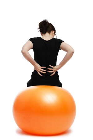 back training: young woman with pain in the back sitting on orange exercise ball