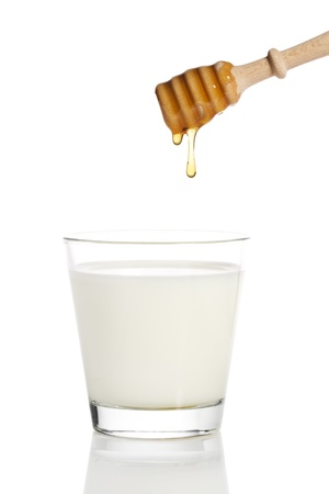 honey drops from a honey dipper in a glass of milk on white background Stock Photo