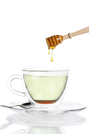 honey drops from a honey dipper in glass cup with green tea on white background Stock Photo - 9559862