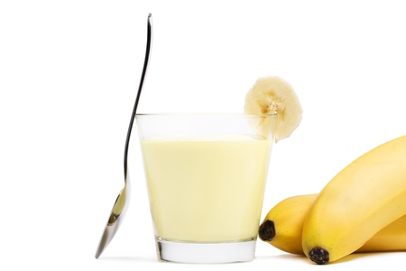 banana milkshake with a piece of banana a spoon and bananas aside on white background Stockfoto