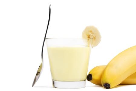 beiseite: Bananen-Milchshake mit einem St�ck Banane einem L�ffel beiseite und Bananen auf wei�em Hintergrund Lizenzfreie Bilder