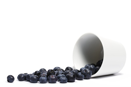 blueberries rolling from a fell over cup on white background