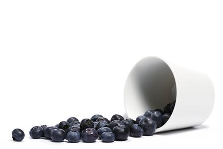 Heidelbeeren, die Rollen von einem fiel Tasse auf weißem Hintergrund Standard-Bild - 10417977