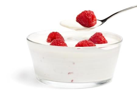 yogurt natural: frambuesa en una cuchara sobre un postre en un bol con las frambuesas en el fondo blanco