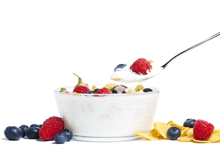 yogurt with blueberries, strawberries, raspberries and cornflakes on white background