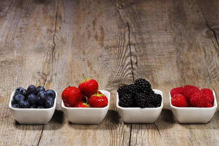 row of wild berries in bowls on wooden background