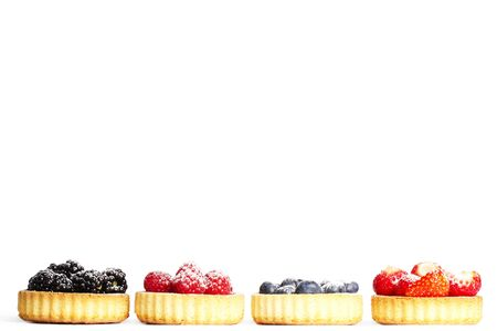 wildberry: row of tartlets with sugar covered wild berries on white background Stock Photo