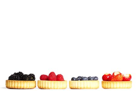 wildberry: row of tartlets with wild berries on white background Stock Photo