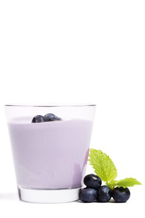 some blueberries with melissa near a milkshake with blueberries on white background Stock Photo