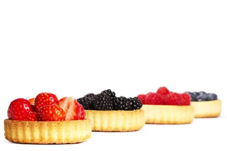 wildberry: strawberries in a tartlet in front of wild berries in tartlets on white background