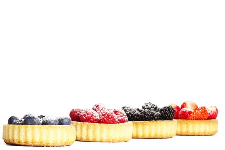wildberry: sugar coveres blueberries in front of wild berries in tartlets on white background