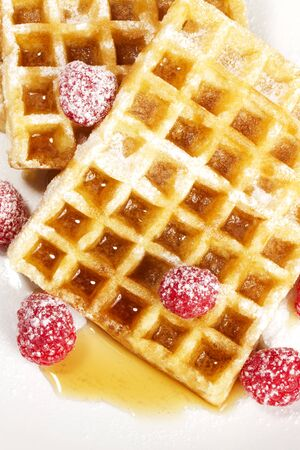 sugar maple: sugar covered raspberries on waffles with syrup from top on white background Stock Photo