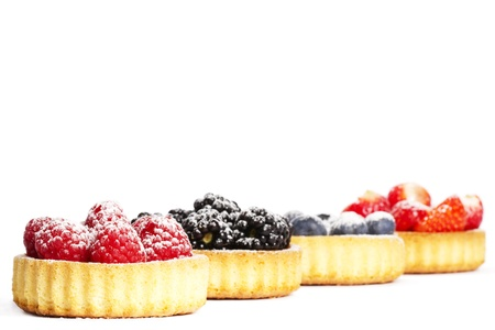 tartlet: sugar covered raspberries in a tartlet in front of wild berries on white background Stock Photo