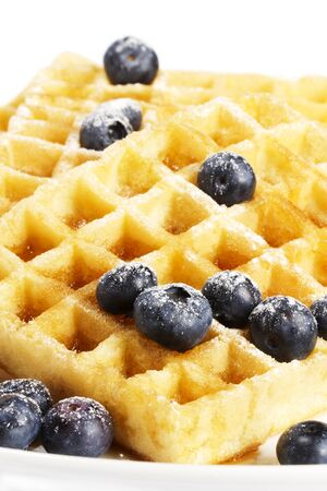 waffles with sugar covered blueberries and syrup on white background photo