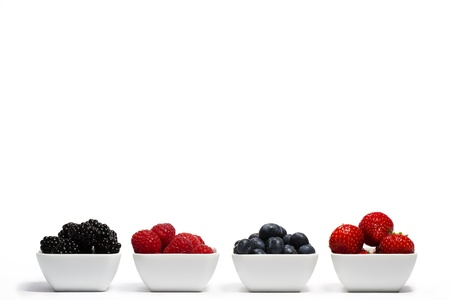 wildberry: row of wild berries in bowls on white background Stock Photo