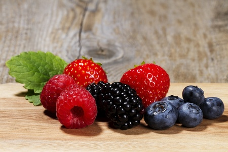 wildberry: wild berries on a chopping board on wooden background