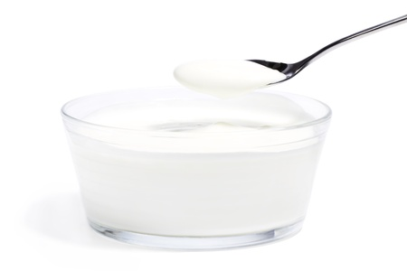yogurt on a spoon over yogurt in a glass bowl on white background Stockfoto