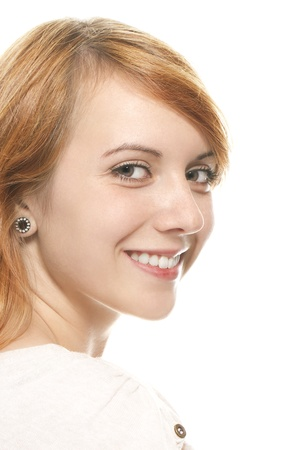 turnaround: portrait of a smiling young redhead woman on white background