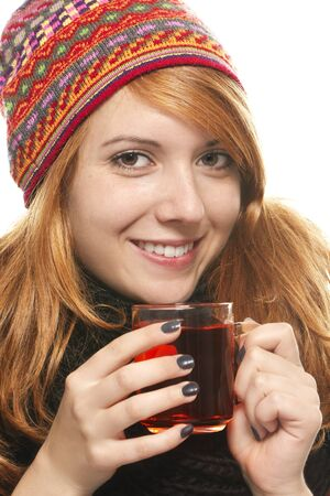 red head: young smiling woman with winter cap warming-up with tea on white background Stock Photo