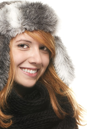 freckled: young happy redhead woman with a winter cap on white background