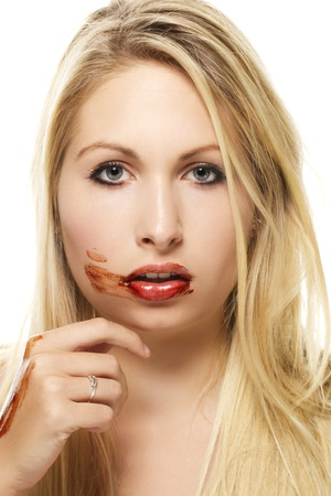 beautiful blonde woman after eating chocolate on white background photo