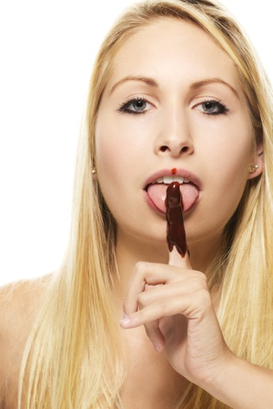 licking finger: beautiful blonde woman licking on her chocolate covered finger on white background Stock Photo