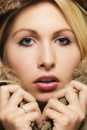 parka: closeup of a beautiful blonde woman wearing a parka with fur