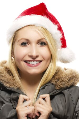 beautiful laughing blonde woman in a parka wearing santas hat on white background photo