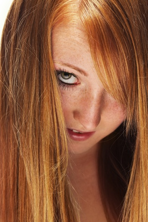 young redhead woman looking through her beautiful hair photo