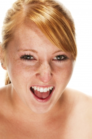 freckles: young redhead woman screaming on white background