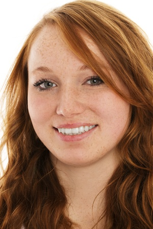 freckles: portrait of a young smiling redhead woman on white background
