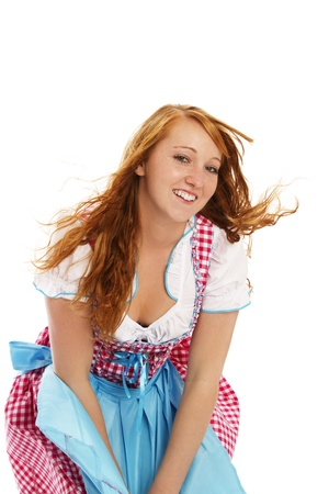 dirndl: woman in bavarian dress handling with wind on white background