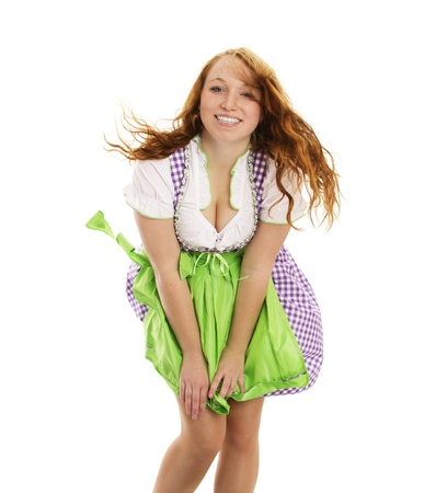 dirndl: young happy woman in bavarian dress handling with wind on white background