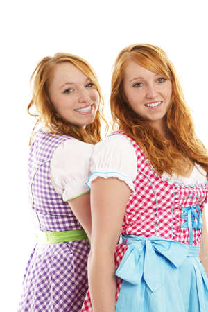 dirndl dress: two bavarian dressed girls on white background Stock Photo