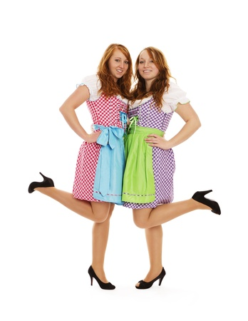 two bavarian dressed girls lifting their feet on white background photo