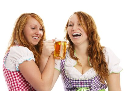 two bavarian girls cheering with beer on white background photo