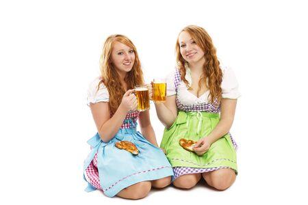 mujer arrodillada: dos niñas de Baviera con pretzels y cerveza de rodillas en el suelo sobre fondo blanco Foto de archivo