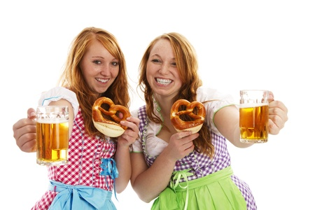 two bavarian girls with pretzels cheering with beer on white background photo