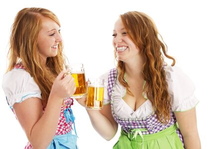 skoal: tow bavarian girls with beer skoaling at each other on white background