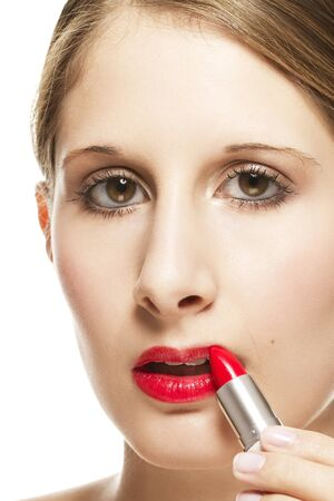 closeup of a beautiful woman applying lipstick on white background photo