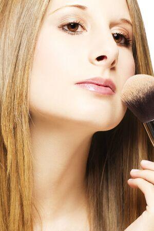smooth hair: beautiful young blonde woman put on makeup