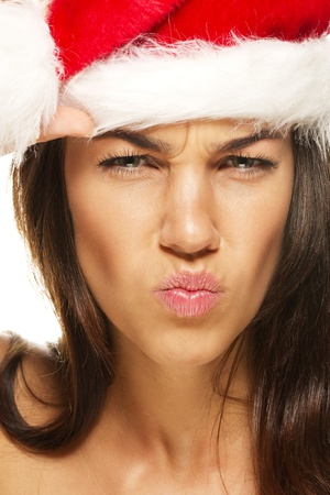 beautiful woman wearing santas hat looking angry on white background photo