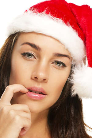 fingertip: young woman wearing santas hat put her fingertip to her mouth on white background Stock Photo