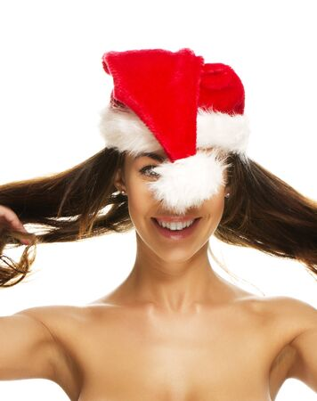 comically: young brunette woman having fun with santas hat on white background Stock Photo