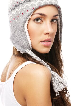 beautiful woman wearing winter cap looking over her shoulder on white background photo