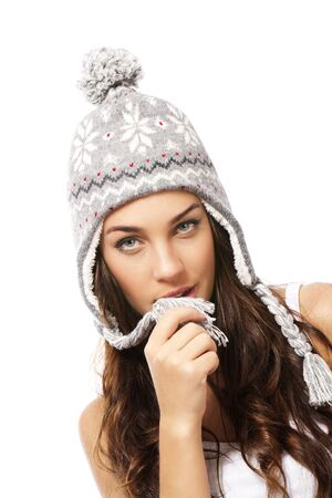 beautiful woman playing with the pompom of her winter cap on white background photo
