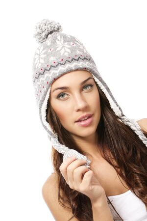 beautiful brunette woman wearing winter cap on white background photo